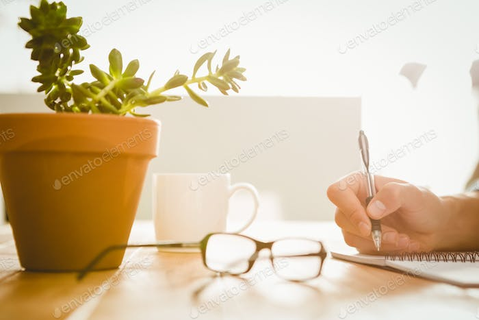 Cropped hand of hipster writing on book at desk in office