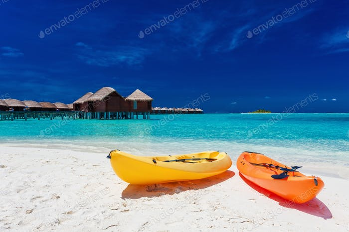 Yellow and orangel kayaks on the tropical beach with vilas