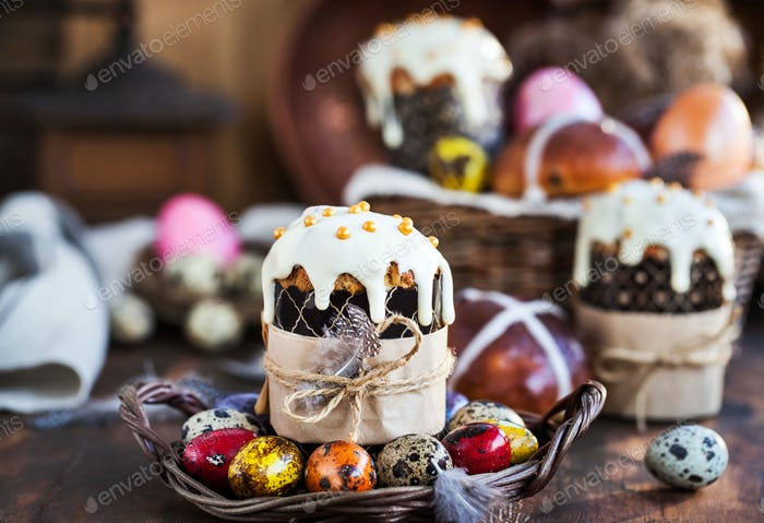 Holiday Easter cakes, hot cross buns and colorful painted eggs on rustic background