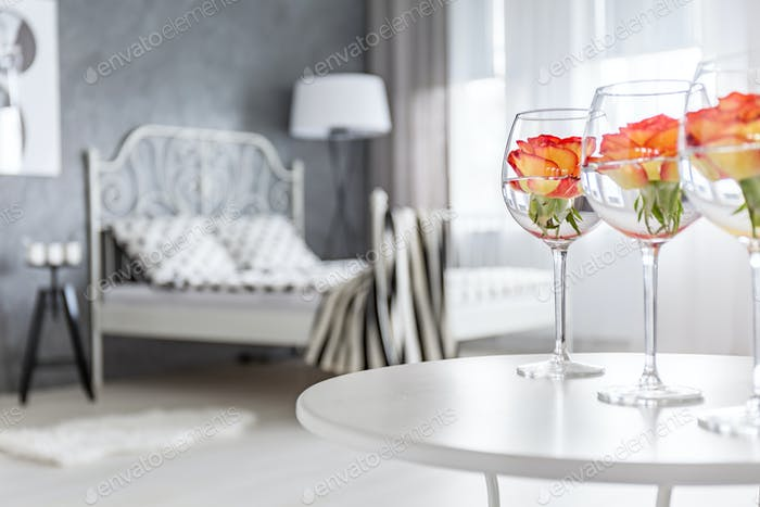Roses in glasses in bedroom