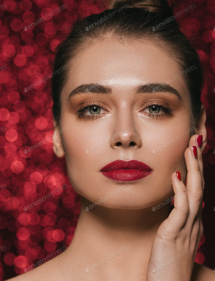Woman face party beauty red lipstick clean skin beautiful female glamour. Red sequins background