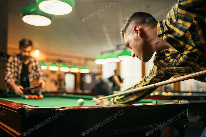 Two male billiard players with cue at the table