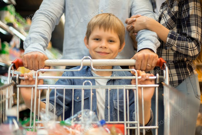 Happy Little Boy Grocery Shopping with Parents