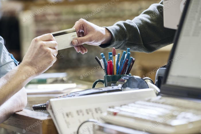 Closeup of hands exchanging a credit card during a retail sale