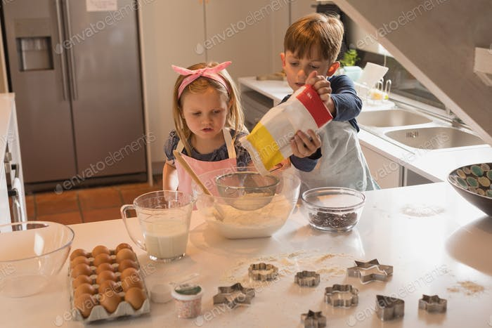 Front view of cute siblings trying to make cookies in kitchen at home