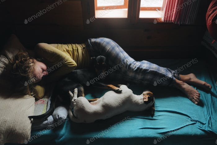 Young caucasian woman laying in bed and playing with her two dogs