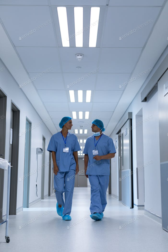 Front view of diverse surgeons talking with each other while walking in the corridor at hospital