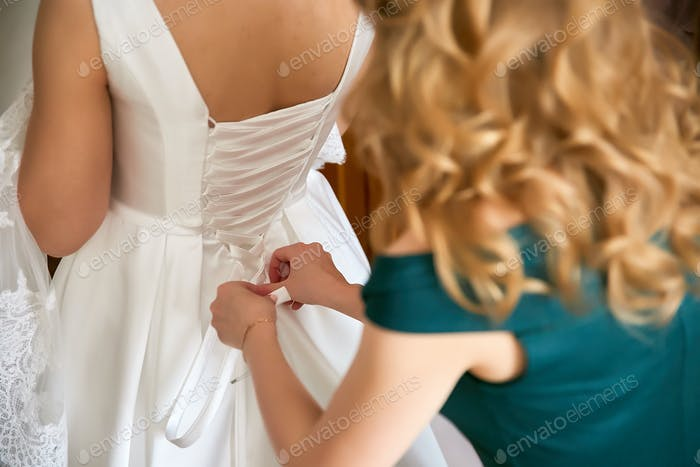 Bride is getting dressed in the room.