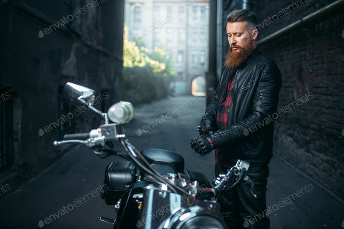 Bearded biker in leather clothes against chopper