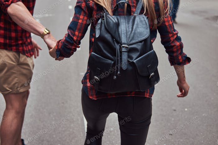 Young hipster couple. Guy teaches his girlfriend to skateboard on the street in a park.