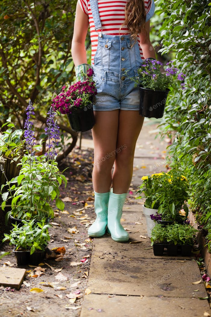 Low section of woman girl with potted plants on footpath