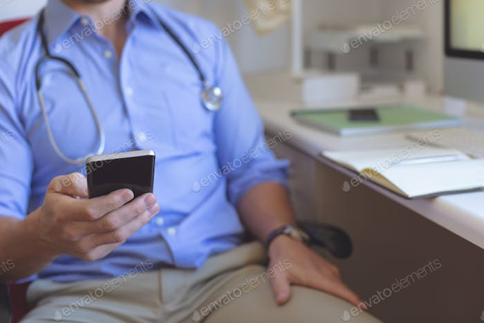 Confident Caucasian male doctor using mobile phone in clinic with stethoscope around his neck