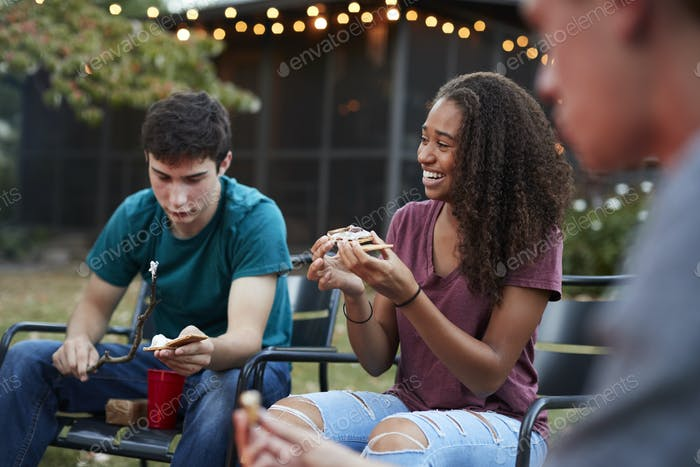 Teenage black girl making sÕmore with friends at a fire pit