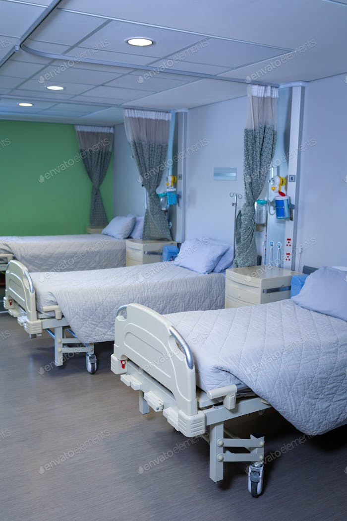 Front view of row of empty hospital beds in hospital