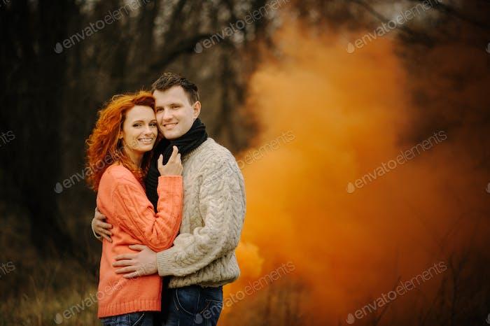 Joven pareja feliz sosteniendo bombas de humo en el camping
