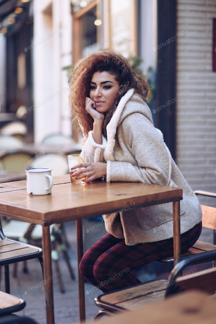 Arab girl in casual clothes drinking a soda outdoors.