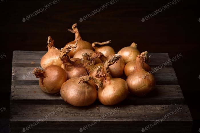 bunch of onions on rustic wood in dark setting