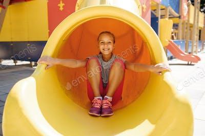 Little girl leisures on playground, childhood