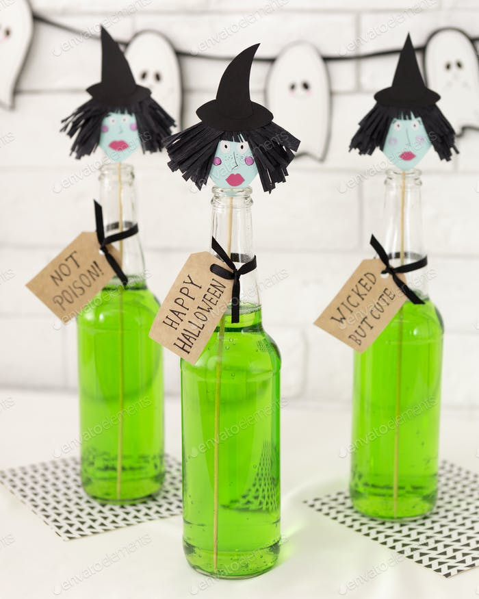 Green toxic cocktail with paper heads on white