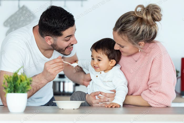 Handsome young father feeding his baby son while the mother looking them in the kitchen at home.