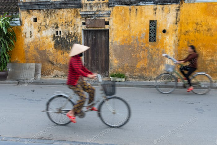 Cyclists on a street in Hoi An, Vietnam.