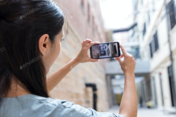 Woman taking photo of the street with cellphone