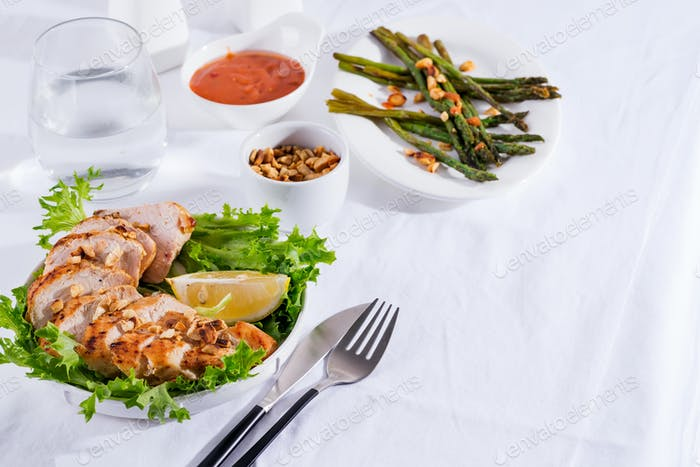 Grilled chicken breast with grilled asparagus and lemon slice. Paleo diet. Healthy nutrition