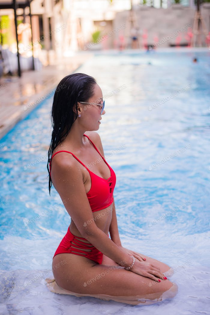 Spending hot summer day poolside. Beautiful young woman in red bikini relaxing by the pool.