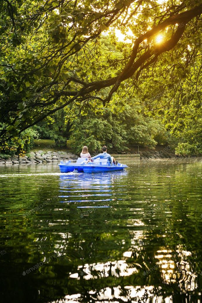 Rückansicht von Freunden Tretboot auf Kanal gegen Bäume