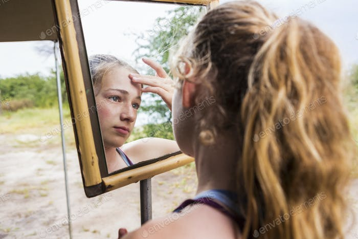 Thirteen year old girl looking into mirror at a tented camp, applying sunscreen to her forehead