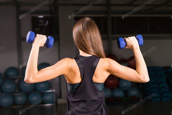 Attractive young sports woman with dumbbells