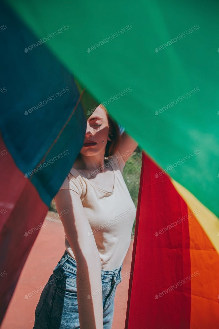Junge Frau bedeckt durch eine Regenbogenfahne