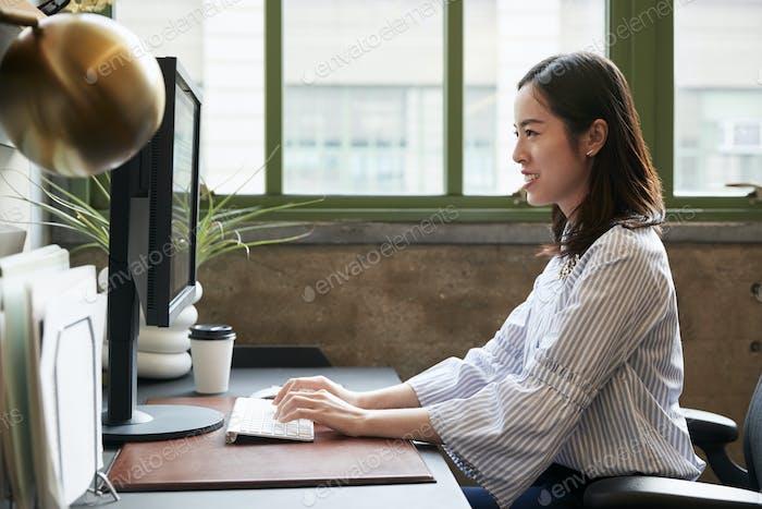 Mujer china Trabajo en un Ordenador en una oficina, vista lateral