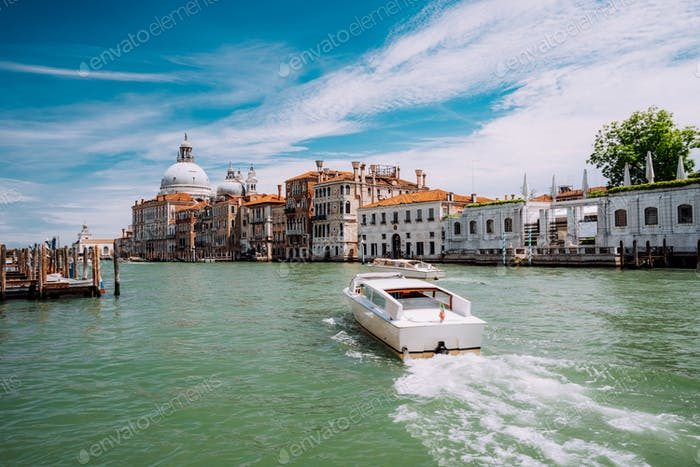 Grand Canal tourist boat with Basilica Santa Maria della Salute against blue sky and white clouds