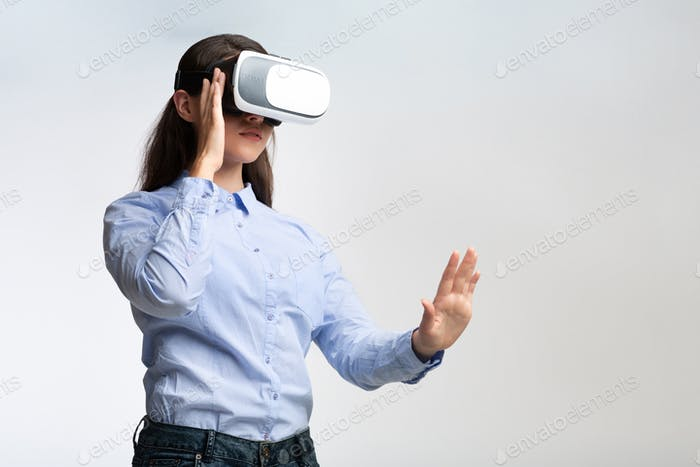Woman In Virtual Reality Headset Touching Invisible Object, Gray Background