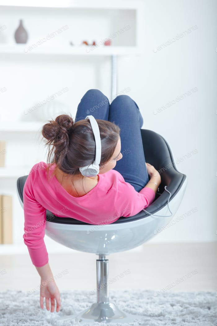 woman listening to music in swivel chair