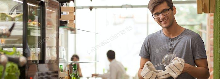 Barman polishing glass in coffeehouse