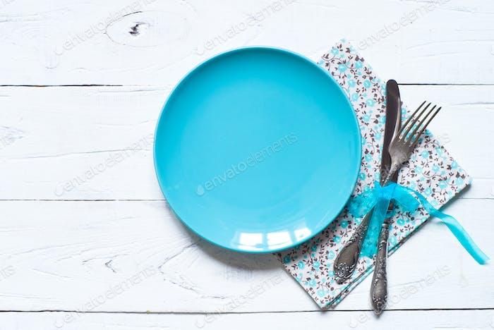 Leere blaue Platte am Holztisch