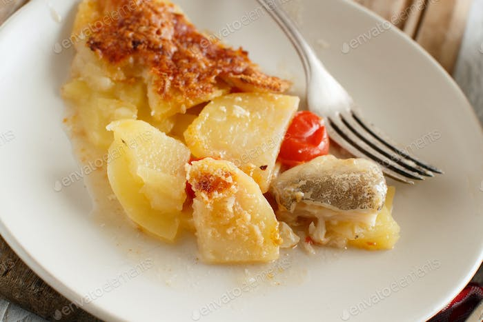 Codfish with potatoes cooked in the oven close up