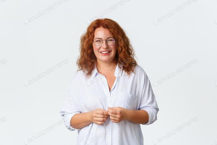 Portrait of smiling lovely middle-aged redhead lady, female entrepreneur or teacher in glasses