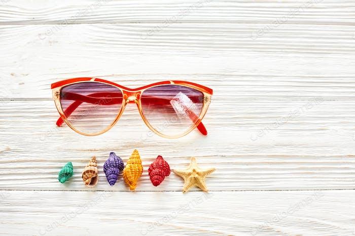 Sonnenbrillen und bunte Muscheln Seestern