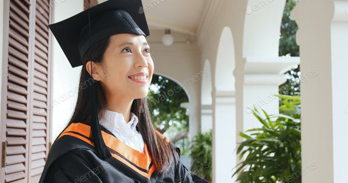 Confident woman with graduation gown in university campus