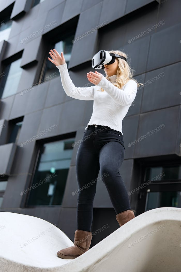 Woman Wearing Virtual Reality Glasses In Front Of Futuristic City Building Wall