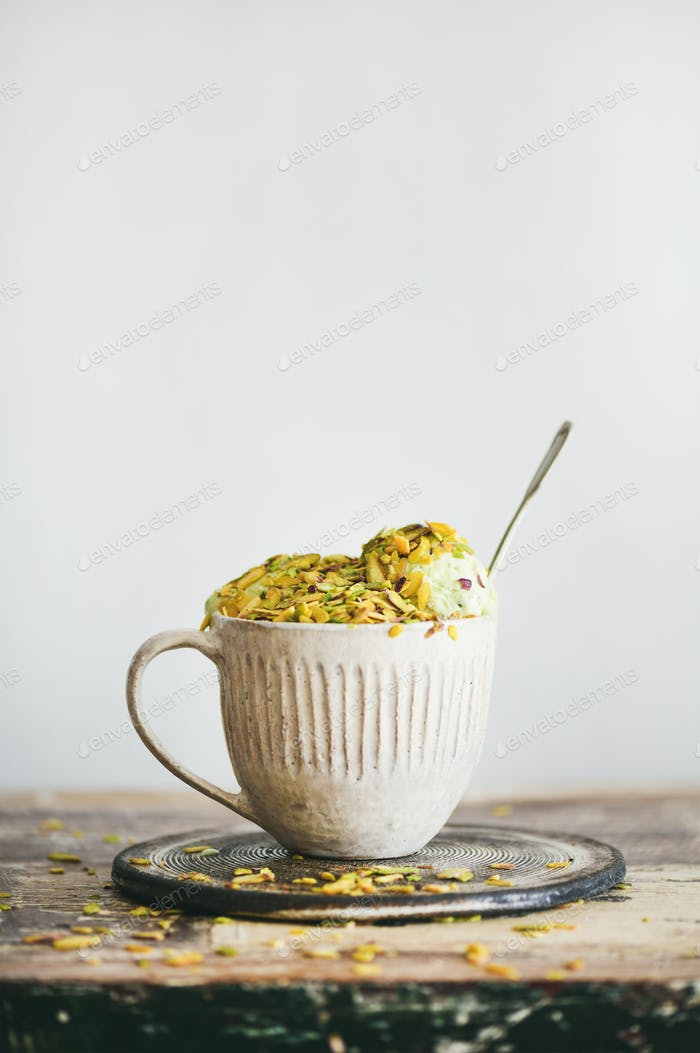 Pistachio ice cream in mug with pistachio nuts, copy space