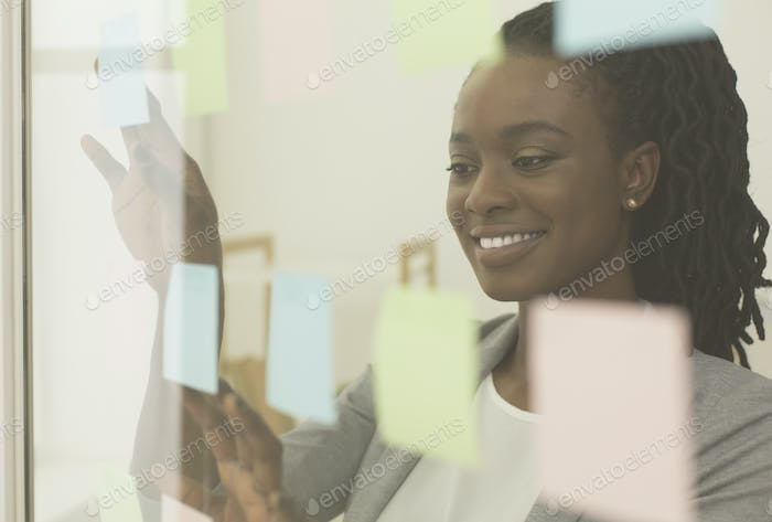 Black Lady Putting Sticky Notes On Visualization Board In Office