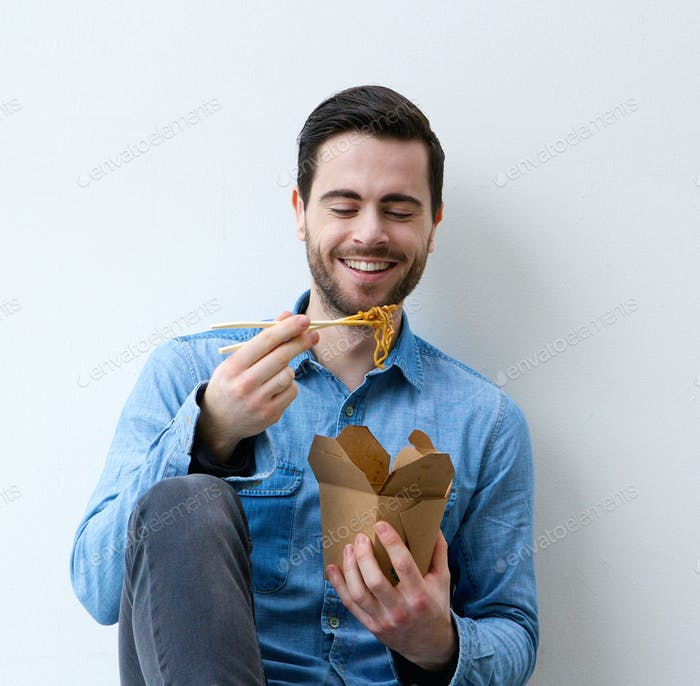 Happy young man eating asian food