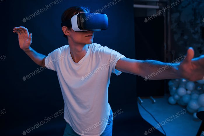 Man, this feels awesome. Young man using virtual reality glasses in the dark room with neon lighting