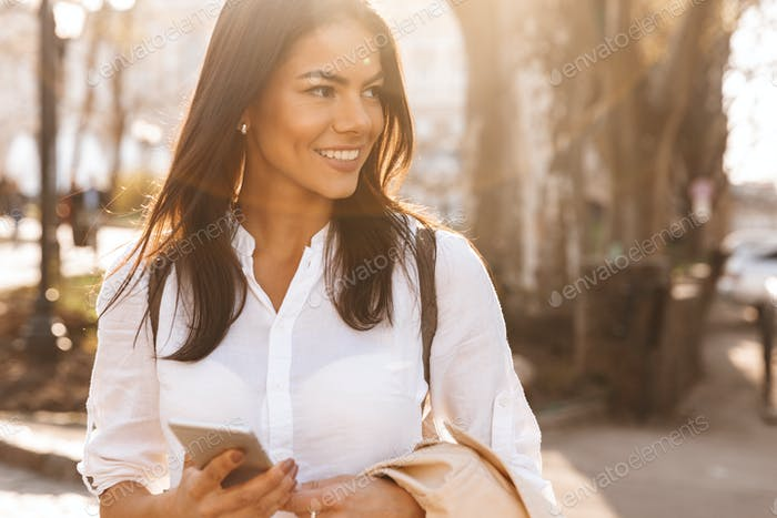 Image of Happy brunette woman in shirt holding smartphone