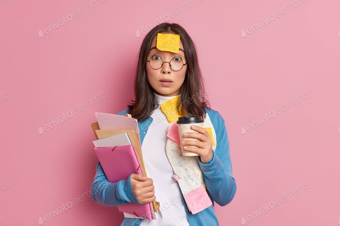 Deadline and overwork concept. Stunned Asian female office worker drinks coffee to go poses with pap