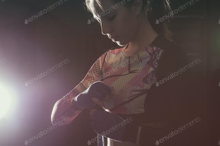 Female fighter putting on boxing gloves prepairing for training